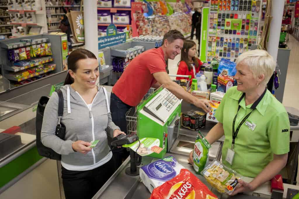Asda retail employee serving woman at checkout.