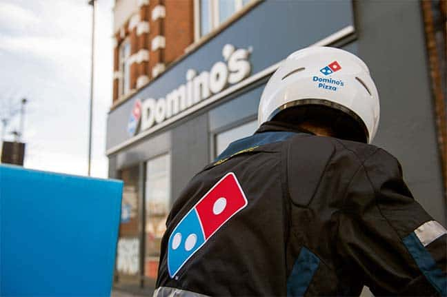 Back of delivery driver wearing Domino's branded jacket and helmet.