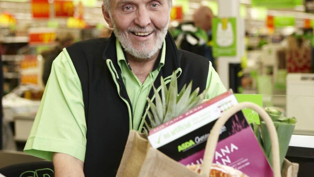 Asda retail employee smiling at checkout.
