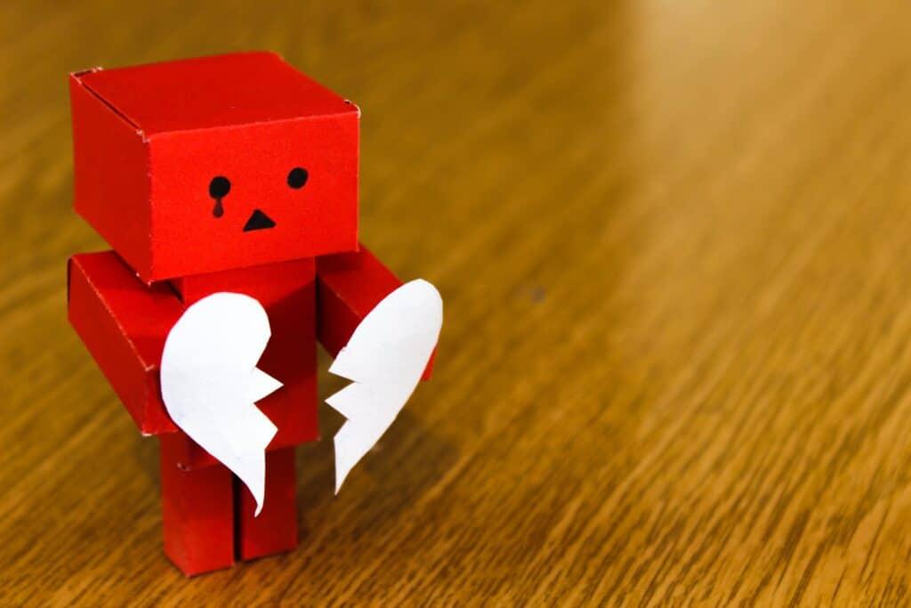 Cardboard robot with broken heart.