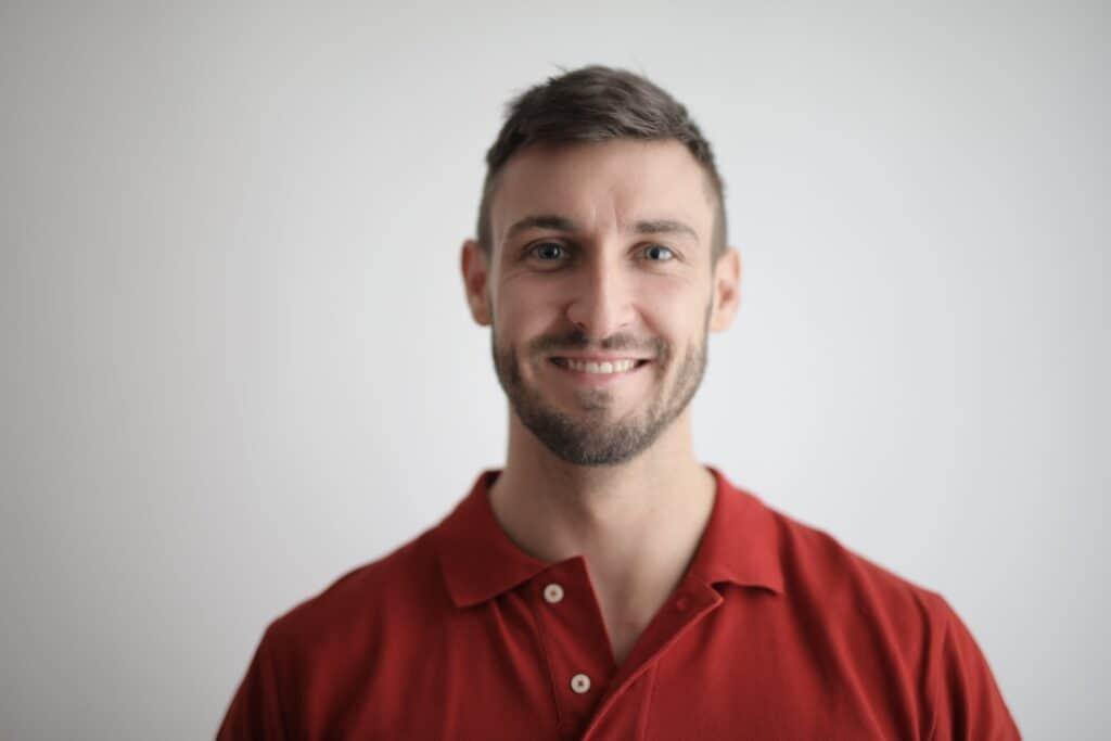Man smiling at camera, plain background.