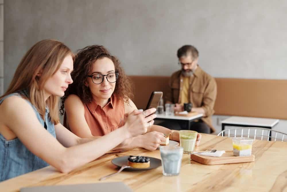 Two women using phone.
