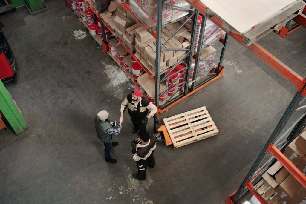 Men in warehouse shaking hands.