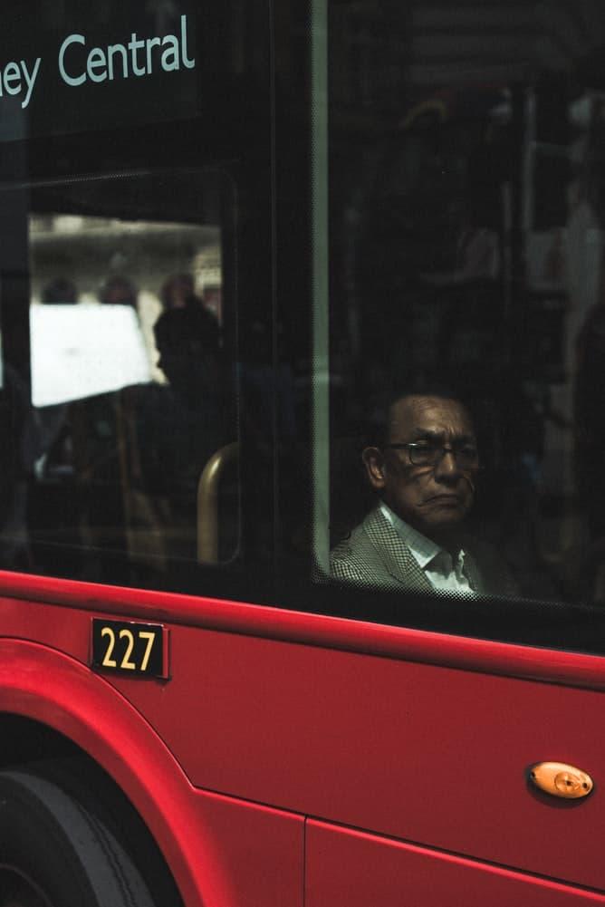Man sat on public transport looking out window.