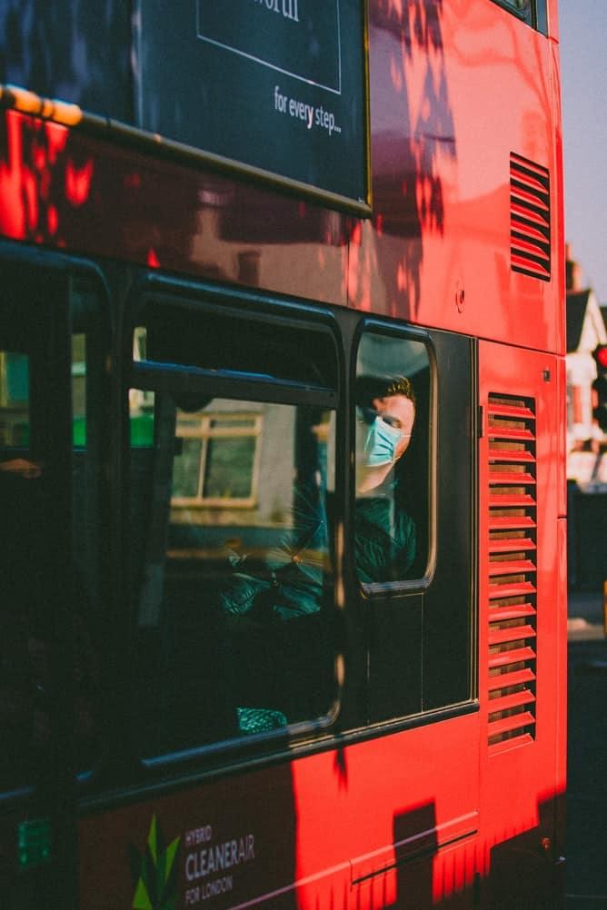 Man sat on bus wearing mask.