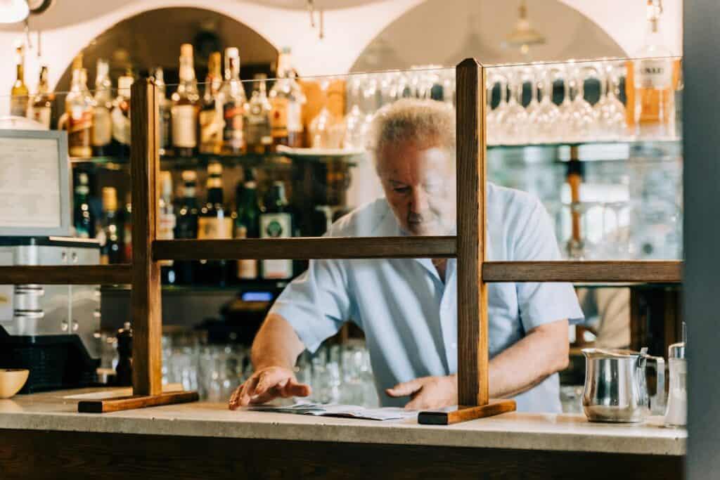 Bartender behind protective screen.